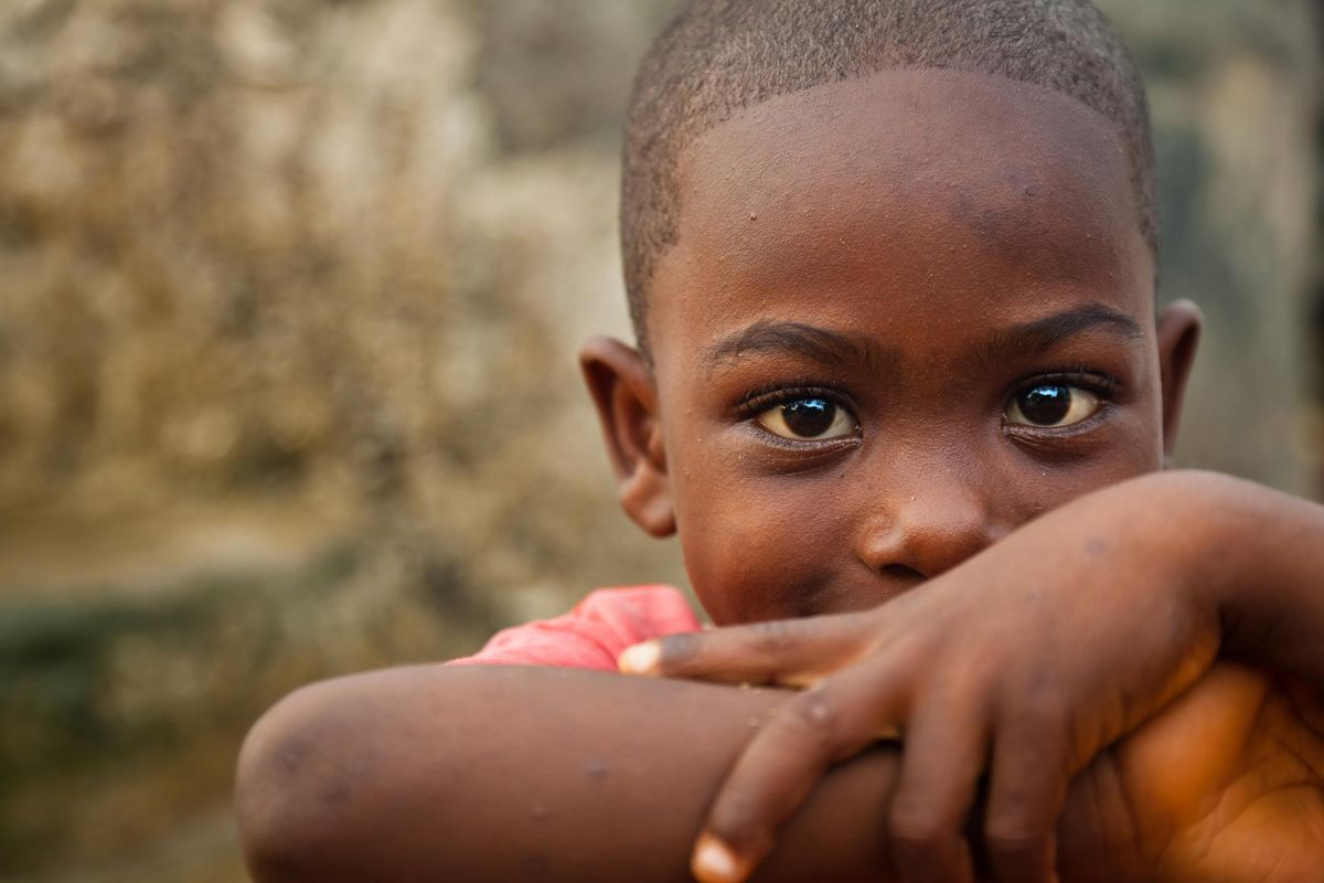 A cute African boy leaning on his elbows and smiling at the camera.