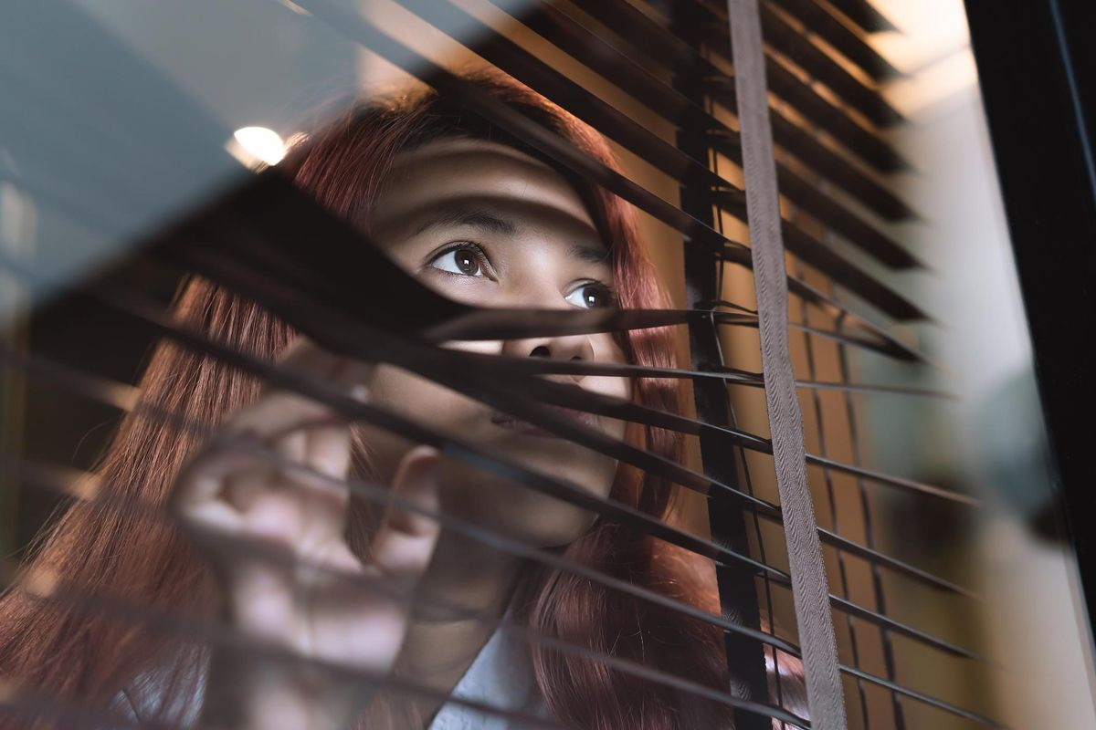 Asian diverse woman looking through window blinds