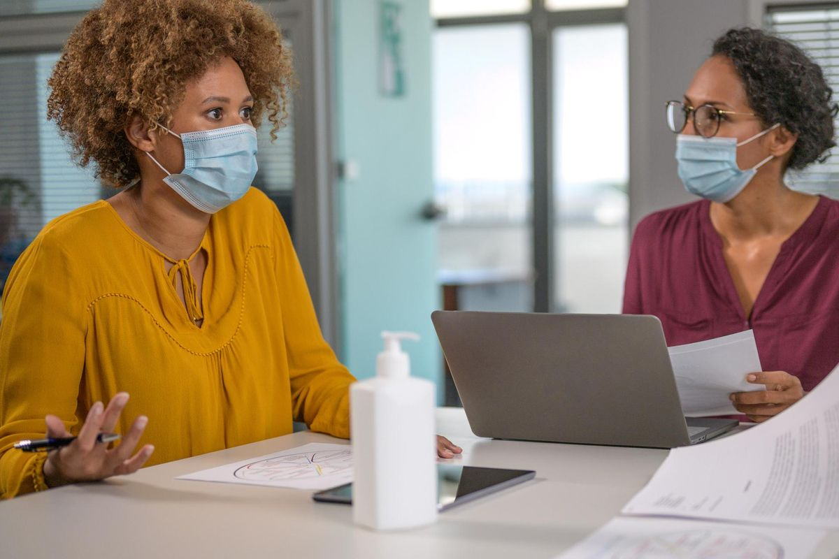 Business people wearing protective face masks at work