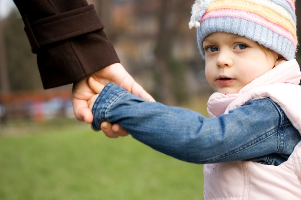 child holding parents hand