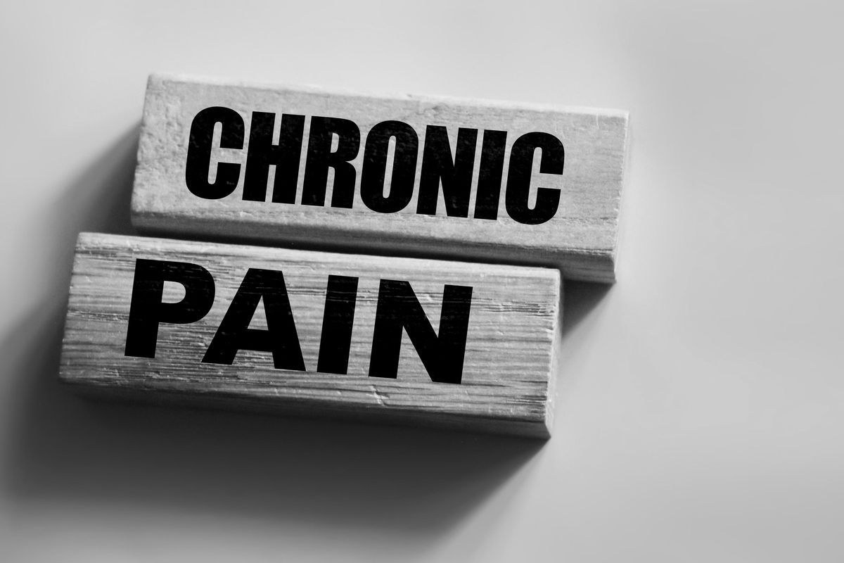 Chronic pain words on wooden blocks on pink with copyspace