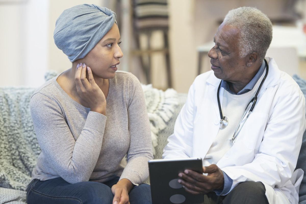Concerned woman with cancer consulting doctor