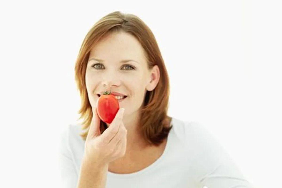 woman eating a tomato