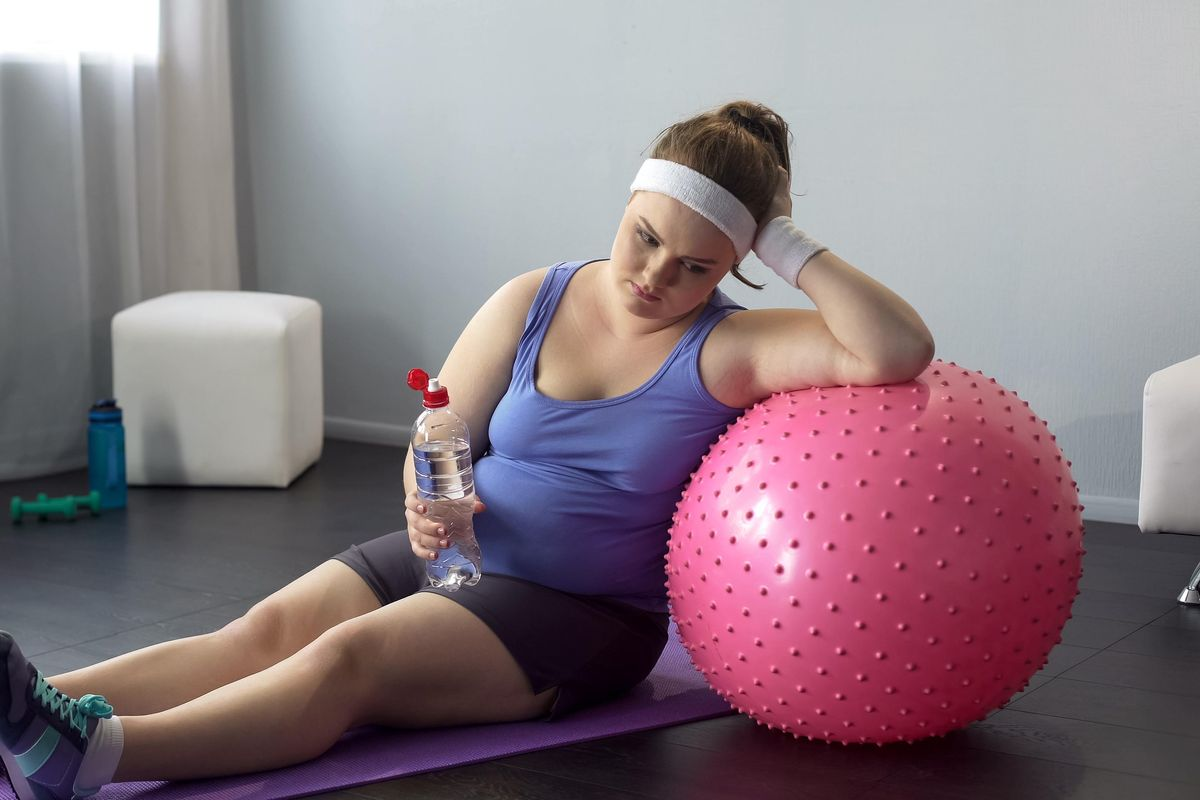 obese lady depressed about her weight unsuccessful workout