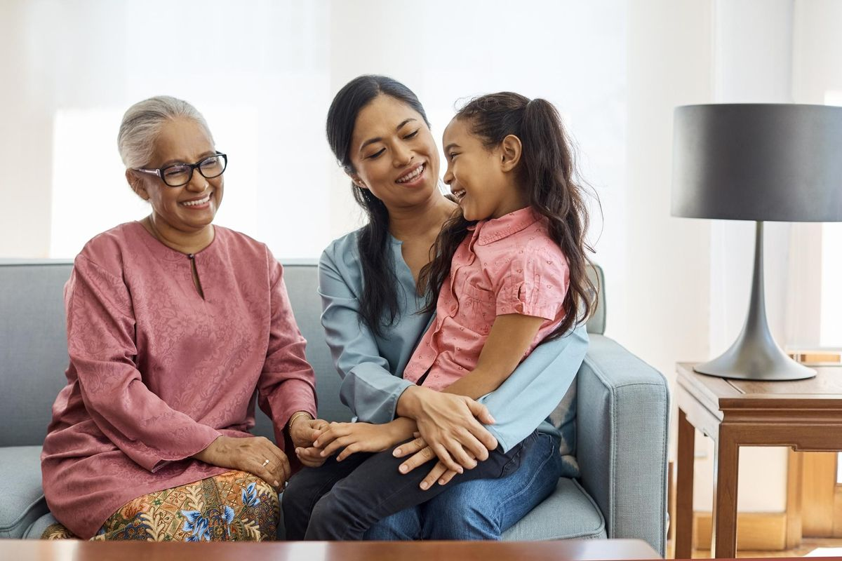 Smiling multi-generational family sitting at home