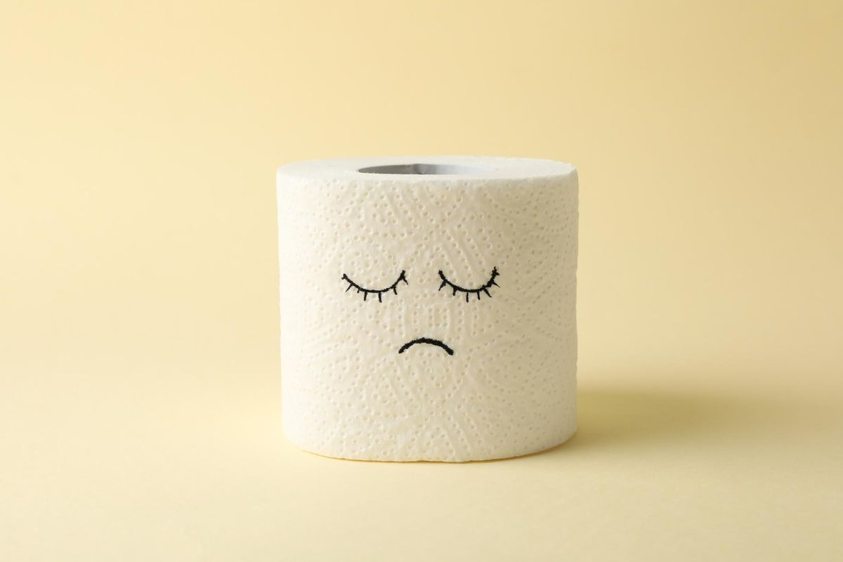 Toilet paper with sad face on beige background