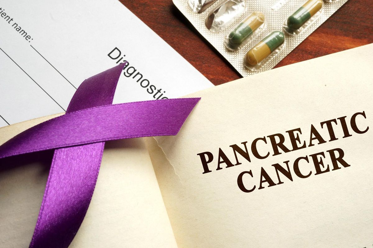 Pancreatic cancer written on a page and purple awareness ribbon