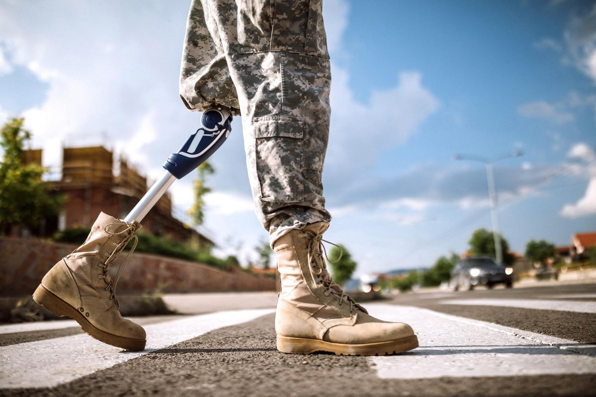 Soldier with prosthetic leg crossing road