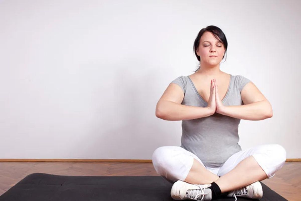 overweight woman practicing yoga