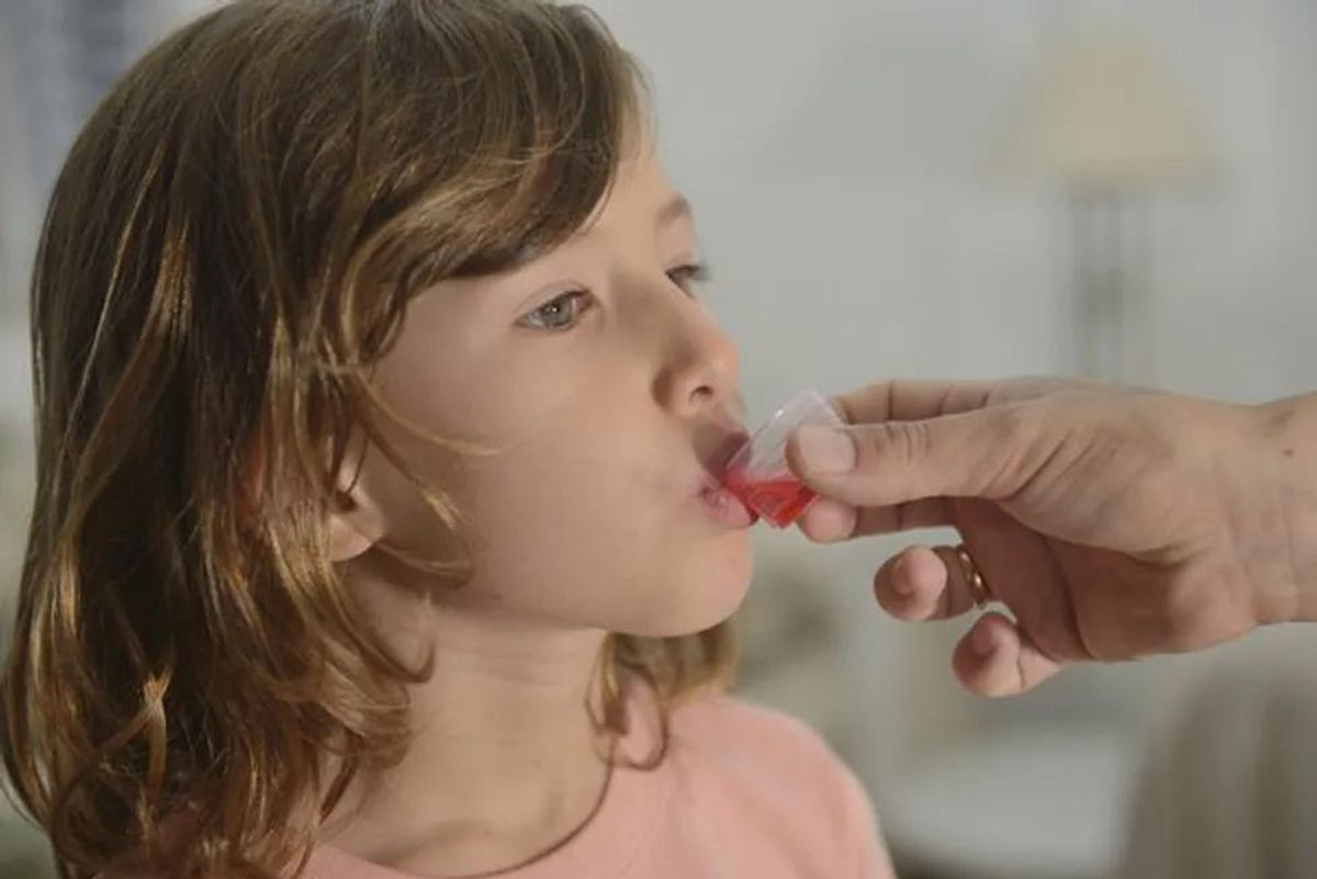 child taking cough syrup