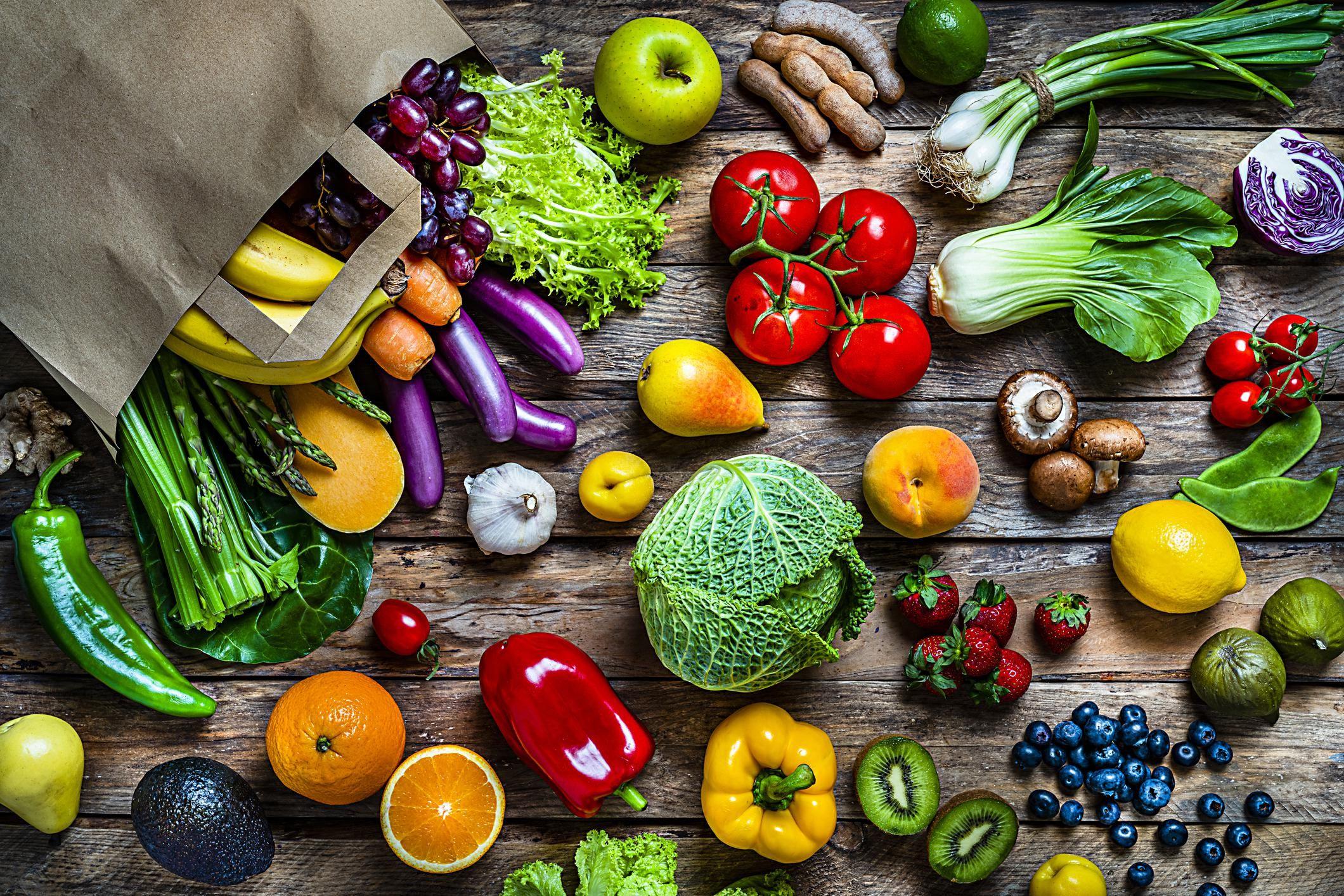 อาหารเพื่อสุขภาพ: ถุงกระดาษสีน้ำตาลที่เต็มไปด้วยผักและผลไม้ออร์แกนิกสดหลากสีที่ถ่ายจากด้านบนบนโต๊ะไม้แบบชนบท  ผักและผลไม้ที่รวมอยู่ในองค์ประกอบ ได้แก่ แอปเปิ้ลสตรอเบอร์รี่กล้วยกีวีส้มลูกแพร์องุ่นมะขามบลูเบอร์รี่พีชมะนาวมะนาวมะเดื่อคะน้ามะเขือเทศสควอชหน่อไม้ฝรั่งมันฝรั่งขึ้นฉ่ายมะเขือม่วงแครอท ผักกาดหอมเห็ดกินได้พริกหวานกะหล่ำขิงหัวไชเท้าอะโวคาโดหัวหอมพริกข้าวโพดและอื่น ๆ