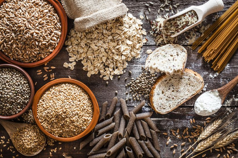 Top view of wholegrain and cereal composition shot on rustic wooden table. This type of food is rich of fiber and is ideal for dieting. The composition includes wholegrain sliced bread, various kinds of wholegrain pasta, wholegrain crackers, grissini, oat flakes, brown rice, spelt and flax seeds. Predominant color is brown.
