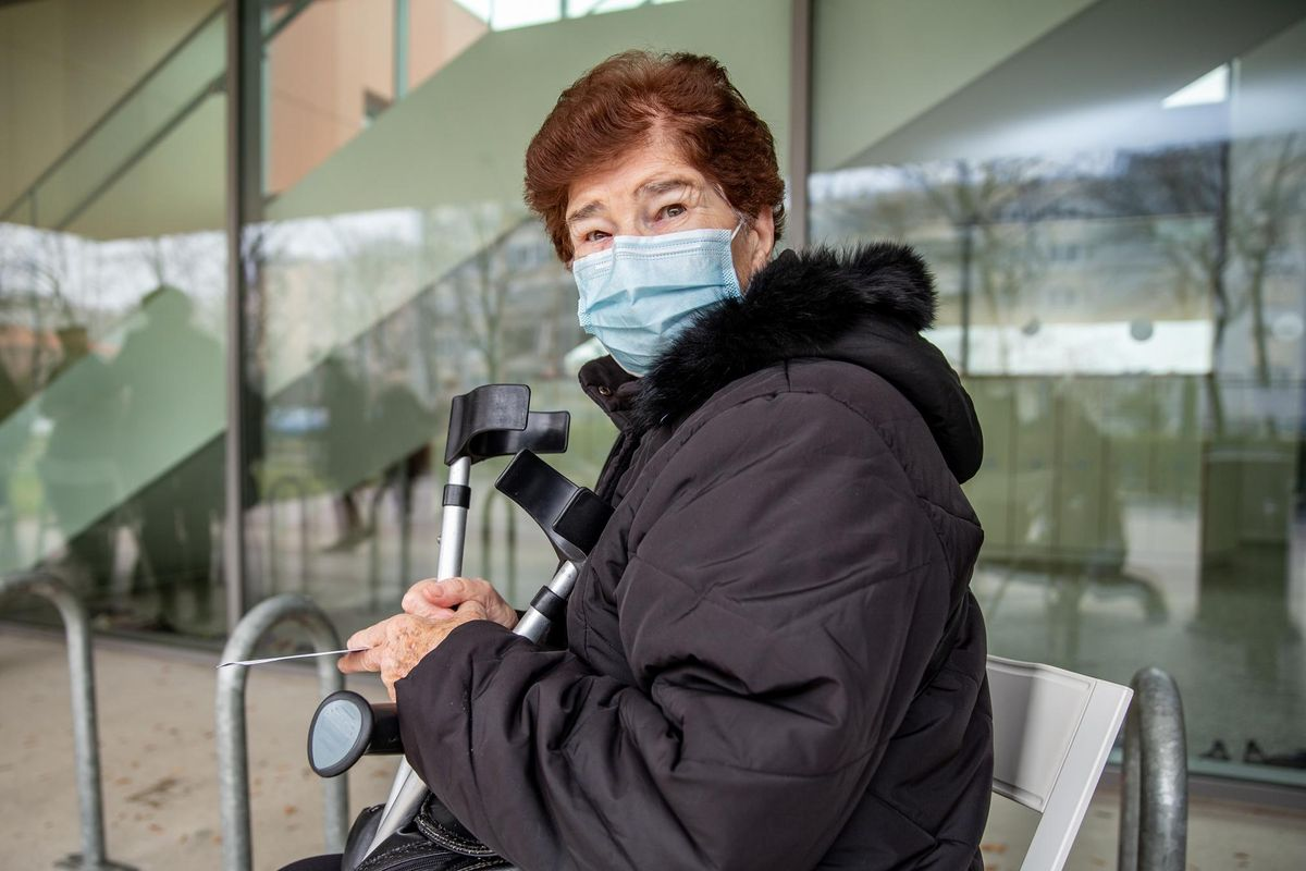 Senior woman waiting outside a Hospital for a COVID-19 vaccination