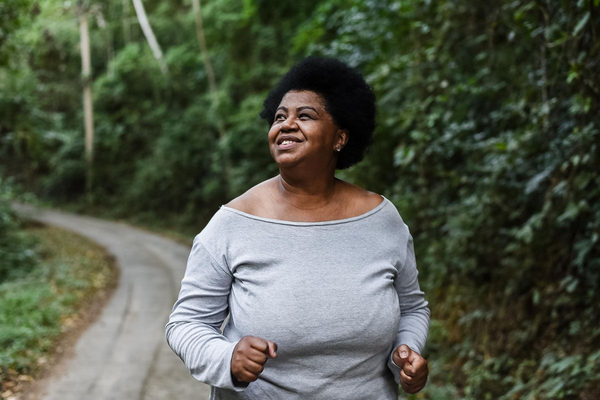 Body positive woman running in nature park