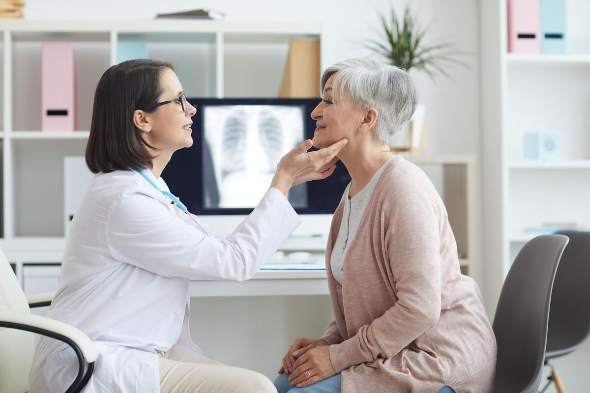 Female Doctor Palpating Neck of Senior Woman