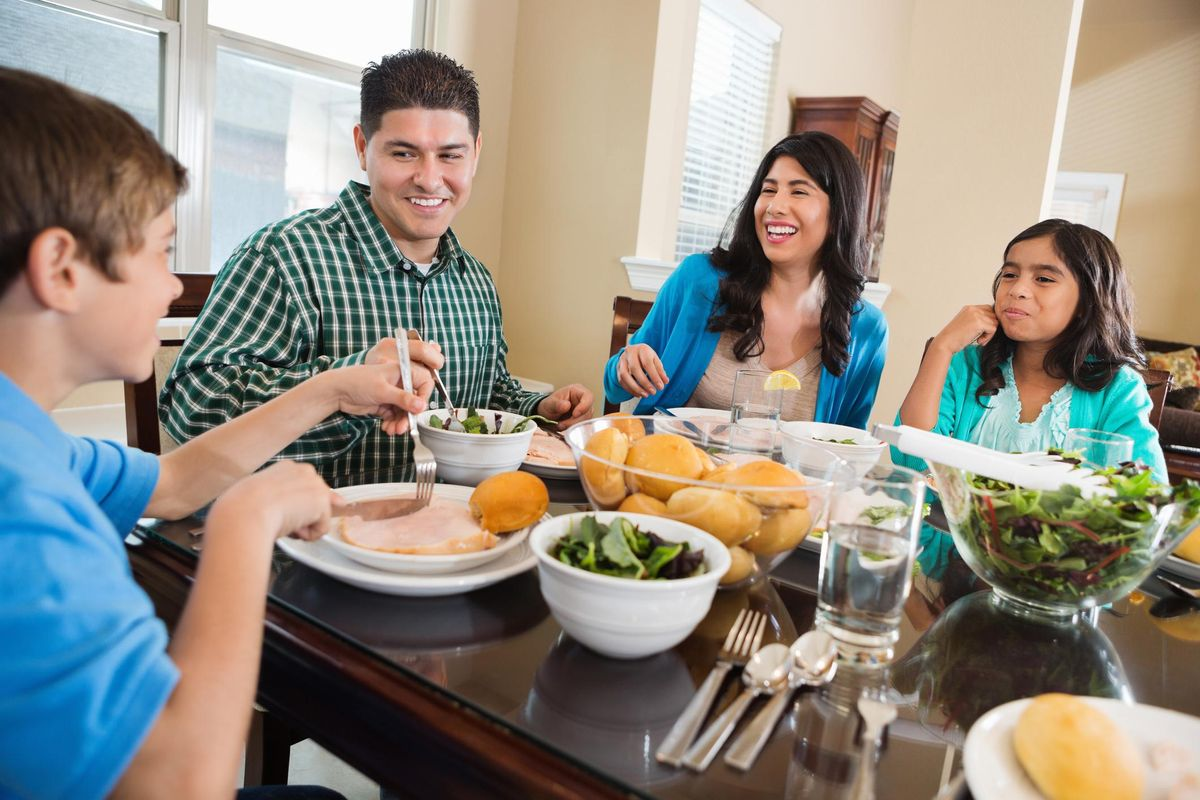Happy Hispanic family enjoying dinner together