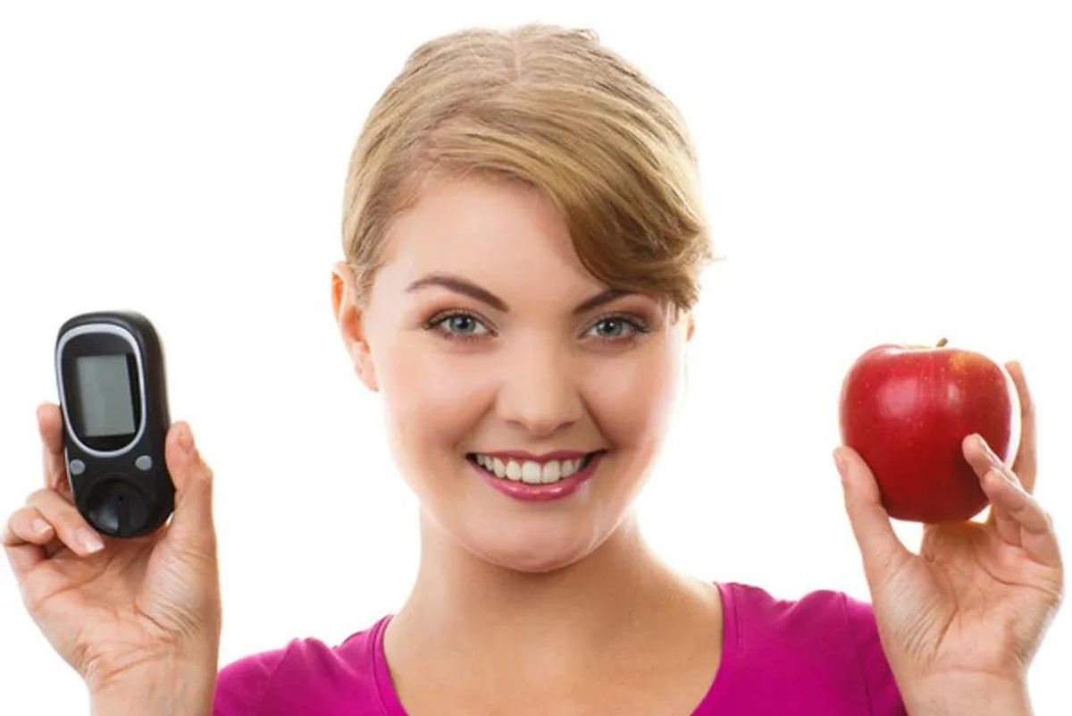 woman holding a diabetes tester and an apple