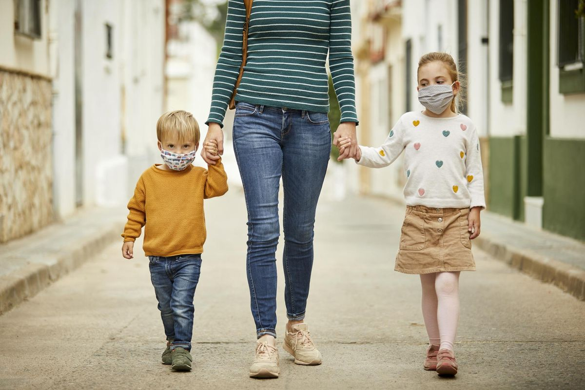 Kids with mother walking on the street with face masks