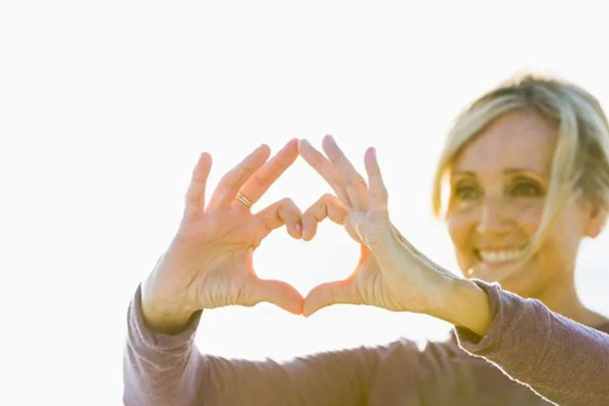woman making the shape of a heart with her hands