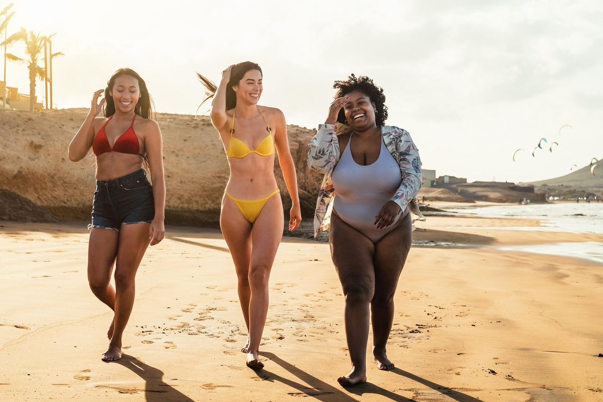 Happy multiracial females with different body size having fun walking on the beach