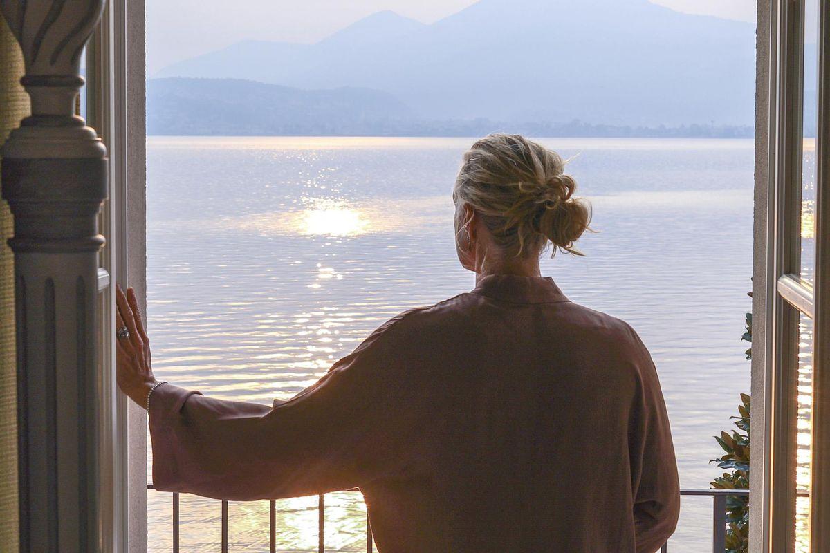 Mature woman walks out to veranda over a lake at sunrise