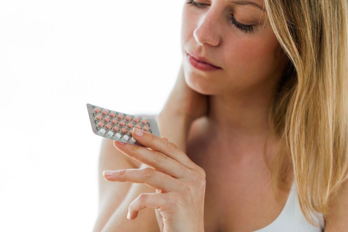 young woman holding contraceptive pills