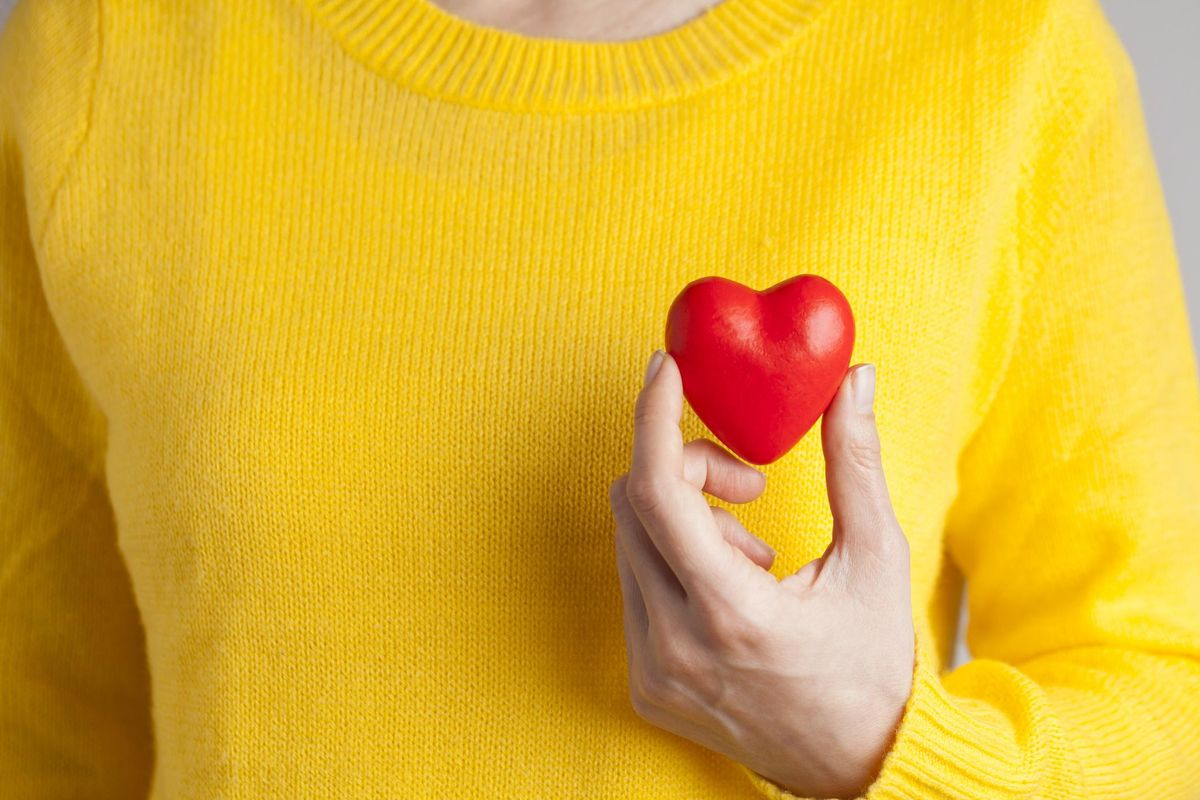 woman holding a plastic shaped heart