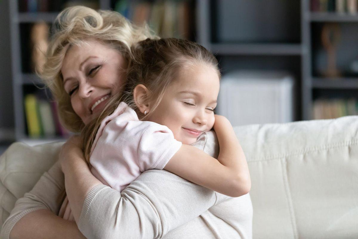 Happy senior granny cuddle with granddaughter