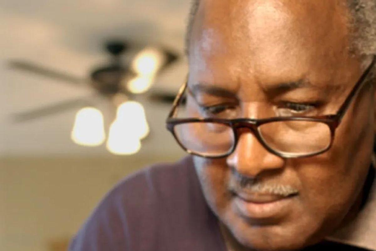 man looking at a blood sugar monitor reading