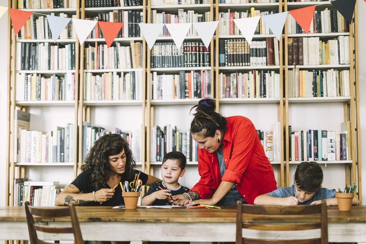 Mothers assisting son in drawing at table. Homosexual parents and children are against bookshelf. Women are with boys at home.