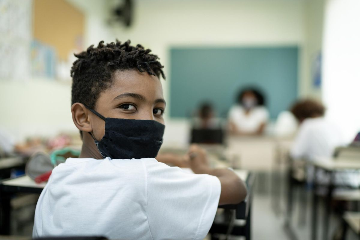 schoolboy wearing a mask, studying in the classroom