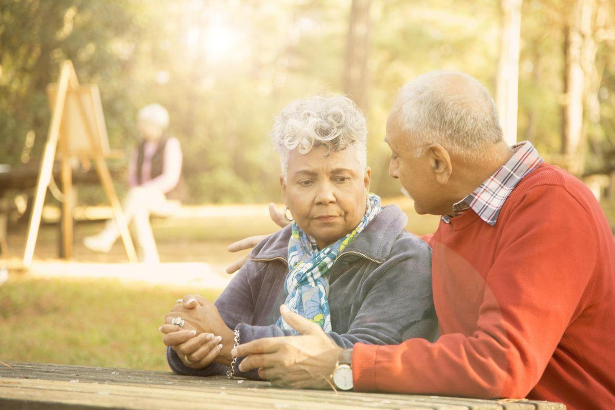 senior adult couple talk at outdoor park
