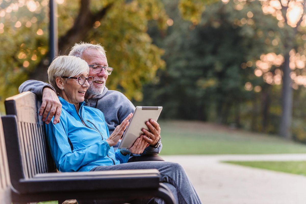 Smiling senior active couple sitting on the bench