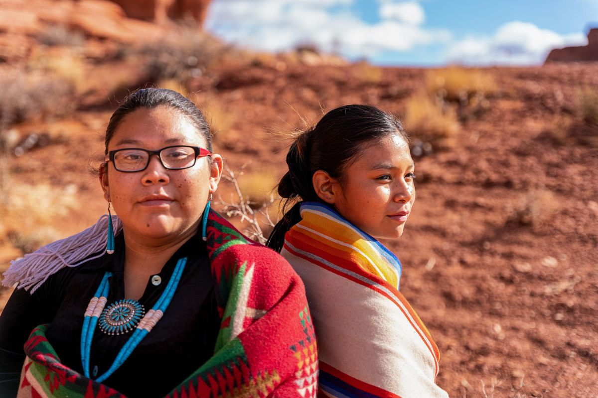 Two Native American, Navajo Sisters Dressed In Traditional Clothing, Wrapped In A Navajo Blanket Sitting Back To Back, One Looking Forward, The Other Looking Away