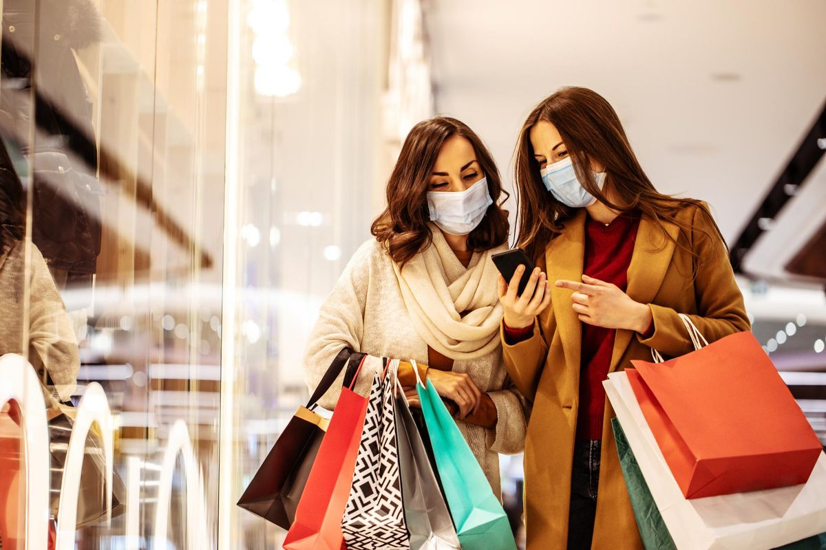 Two young girl friends in safety medical masks during shopping in the mall