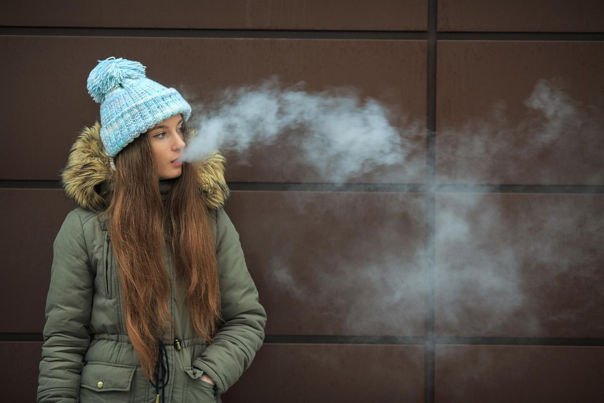 Vape teenager. Young pretty white girl in a cap smoking an electronic cigarette opposite modern brown background on the street in the winter. Bad habit. Close up.