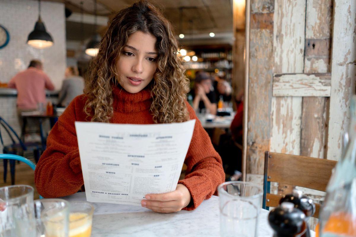 Woman at a restaurant reading the menu