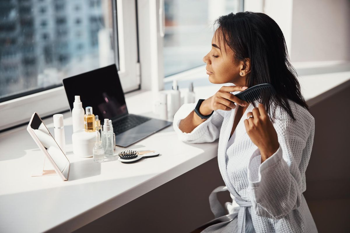 woman brushing hair at home