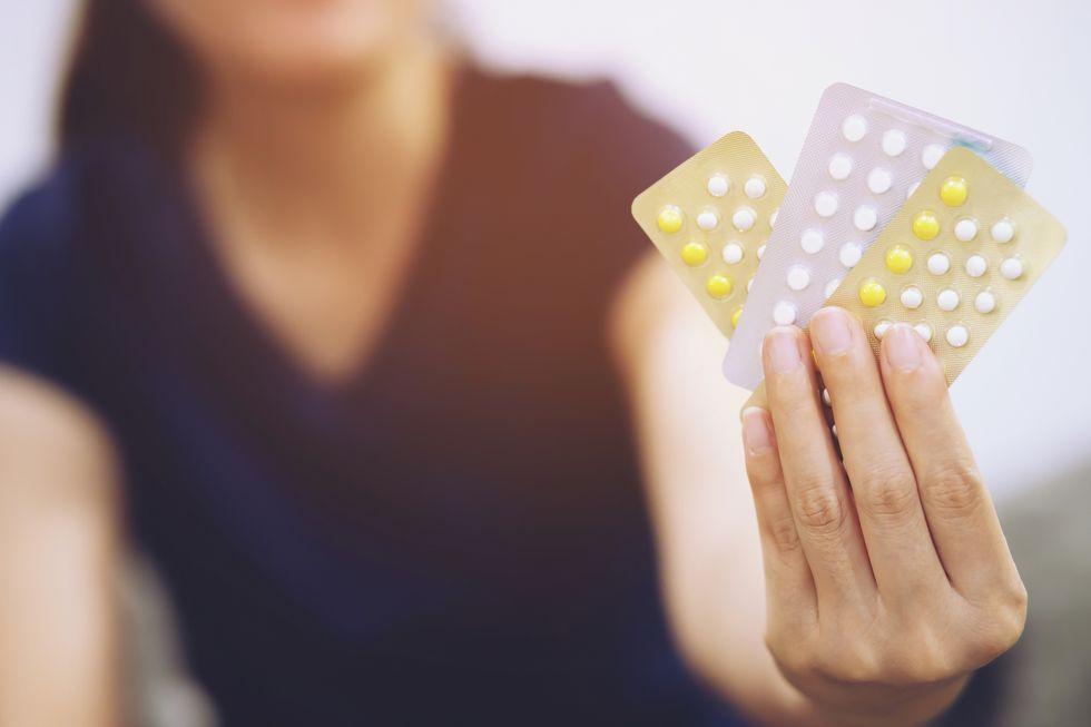 woman holding birth control pills