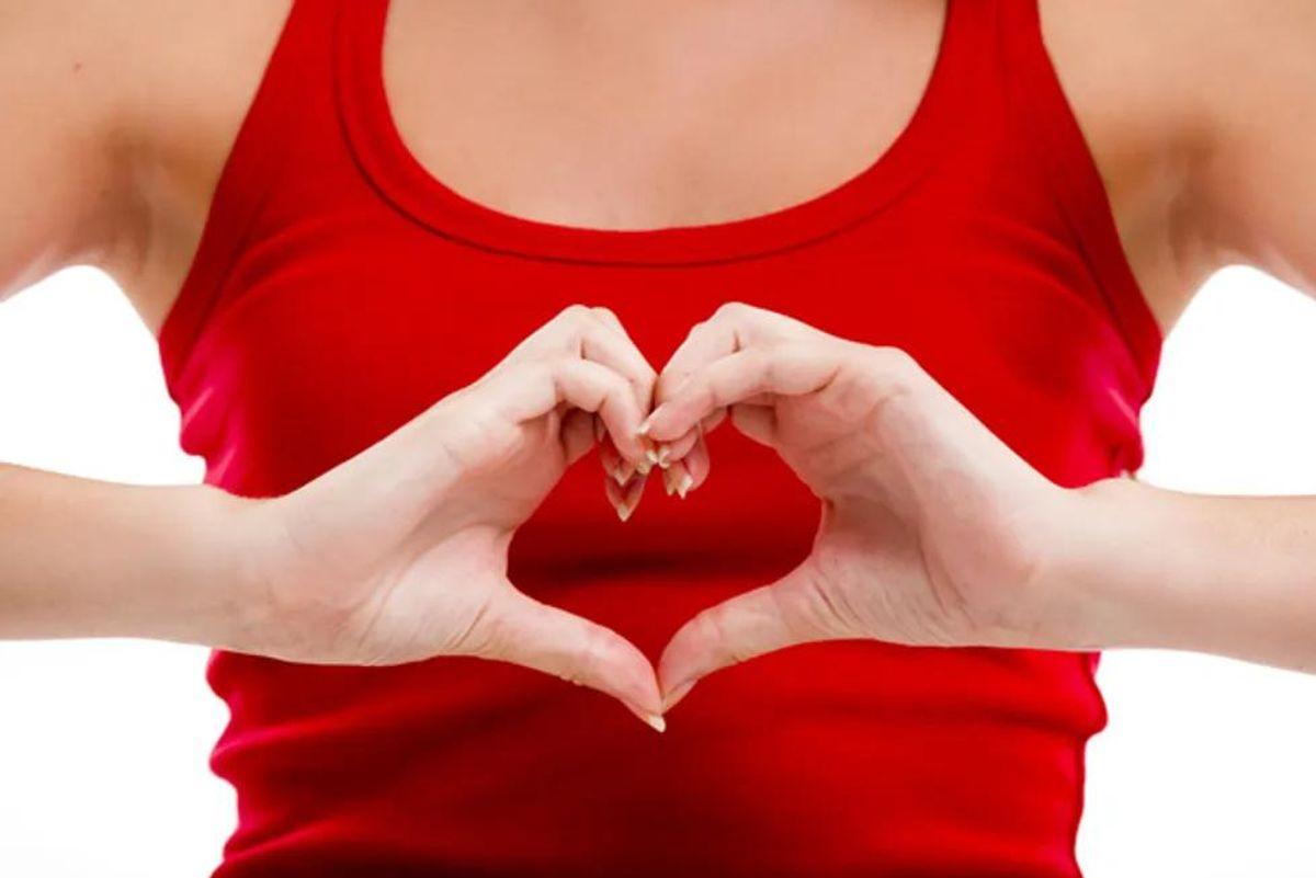 woman holding her hands in the shape of a heart