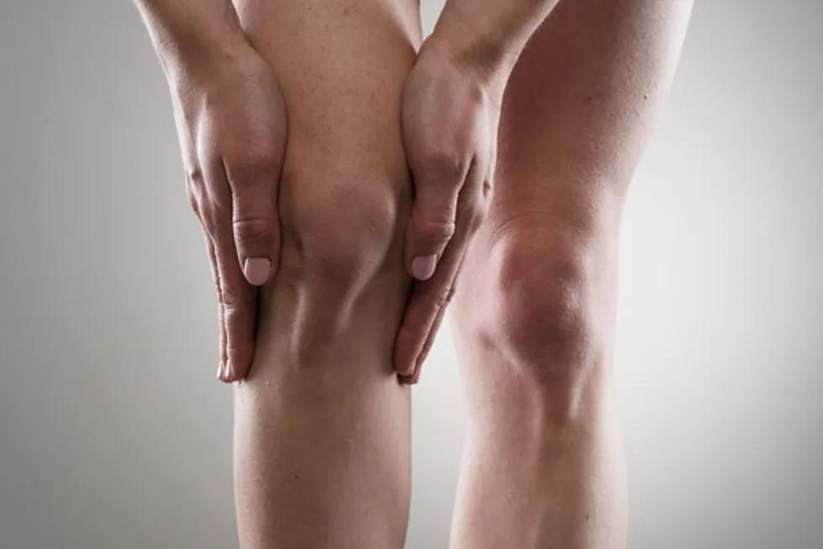 woman holding her knee