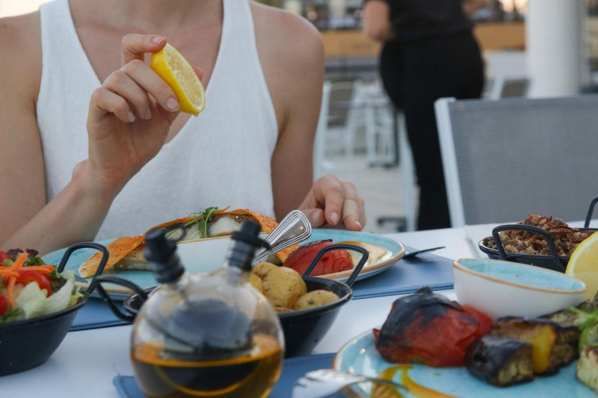 Woman squeezing lemon over a meal