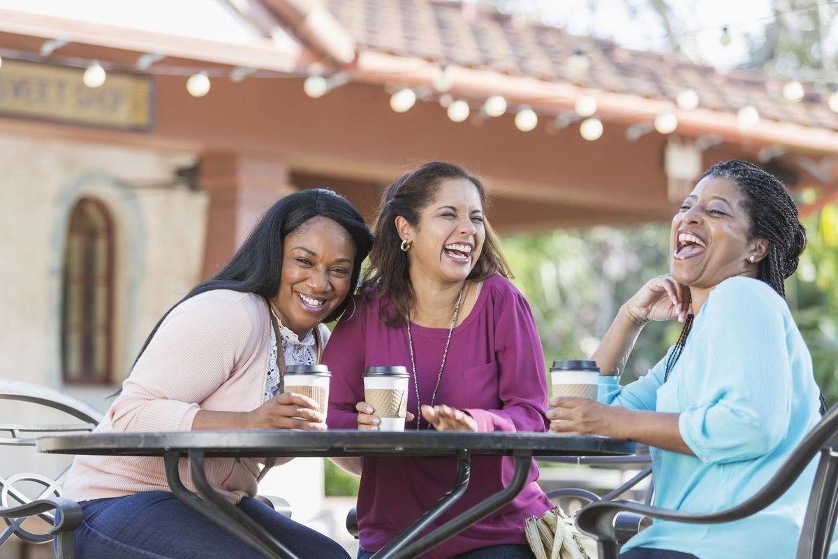 Women at sidewalk cafe drinking coffee, laughing