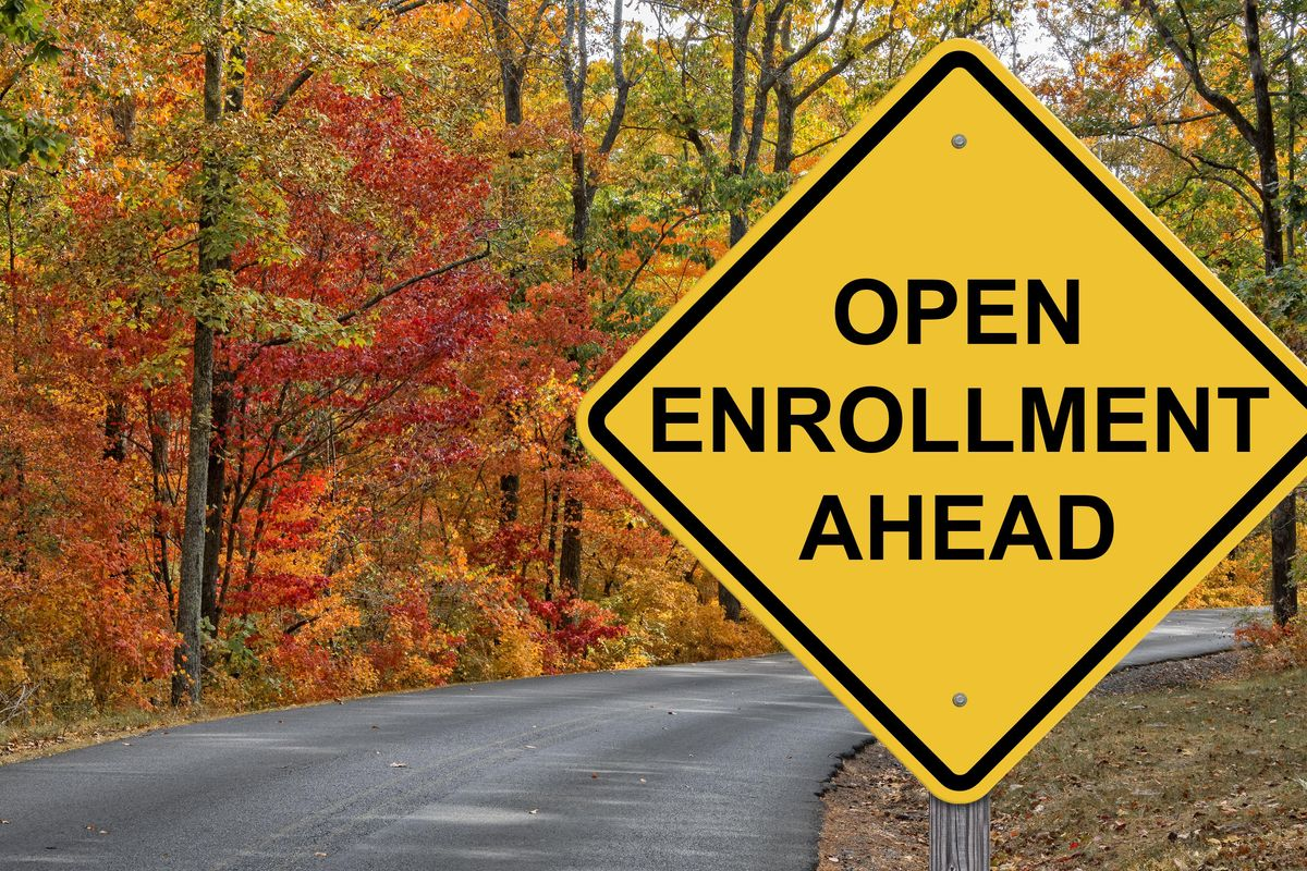 Yellow road sign on a tree-lined street reads: open enrollment ahead.