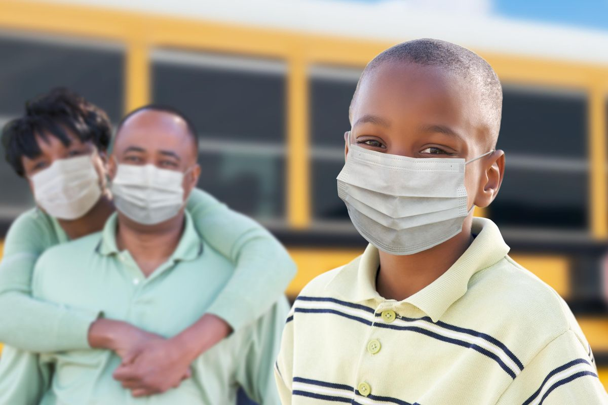 Young African American Student and Parents Near School Bus Wearing Face Masks