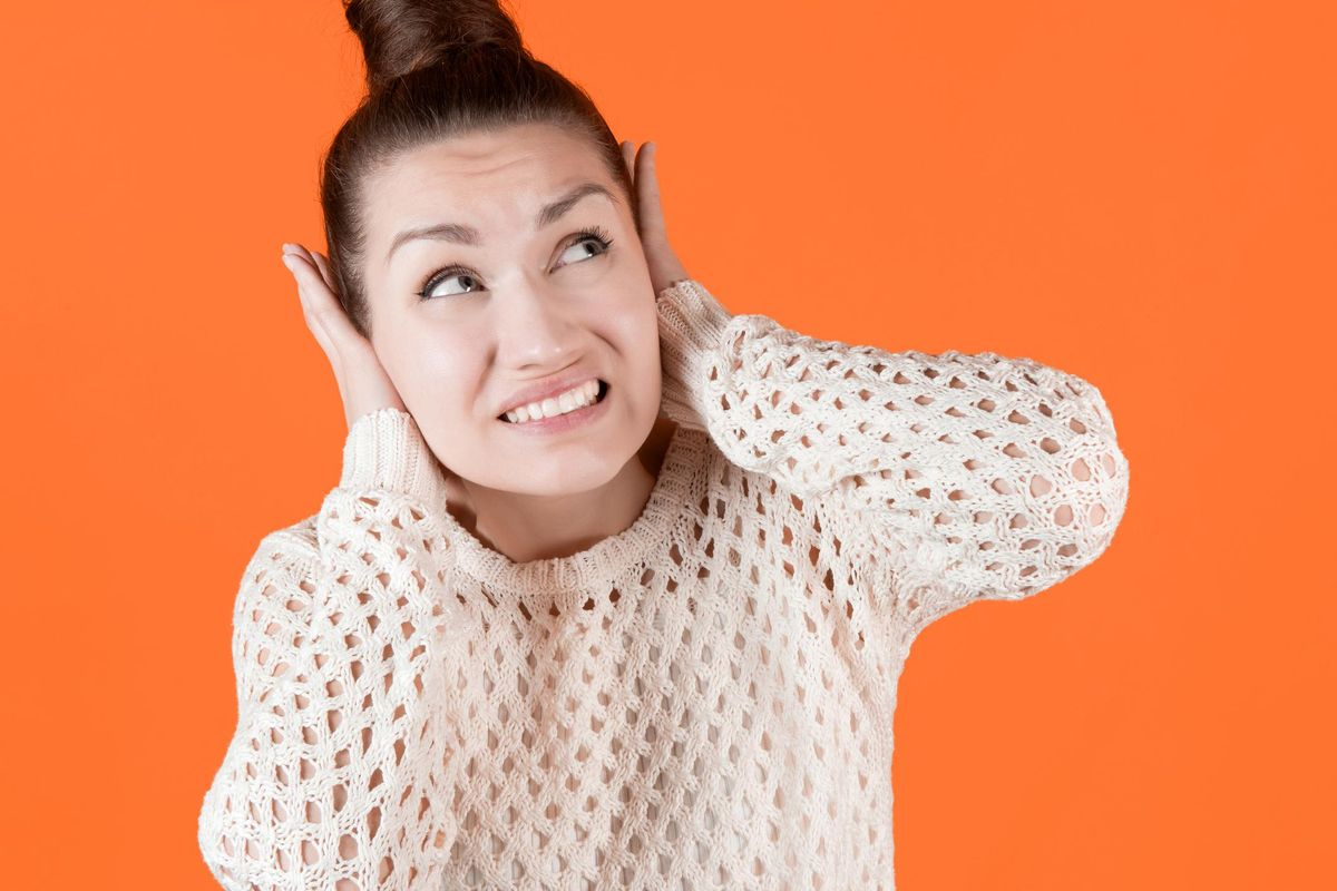 Young woman tightly covers her ears with her hands